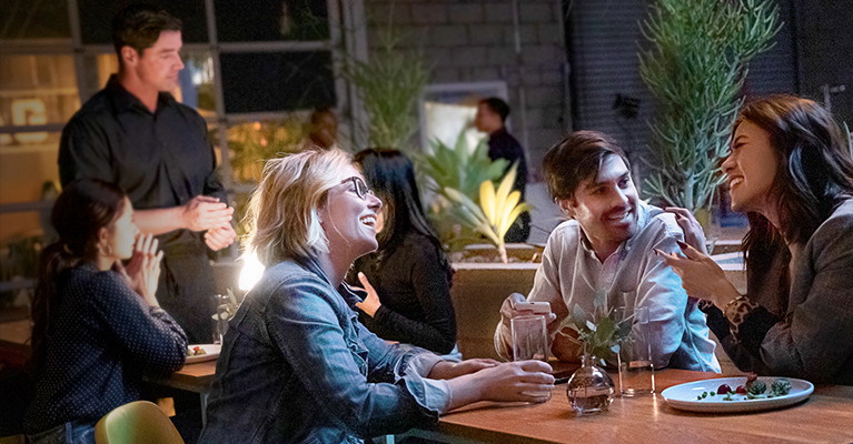 man and two women at a restaurant laughing and talking